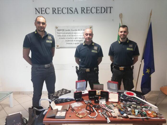 La Guardia di Finanza con gli oggetti sequestrati