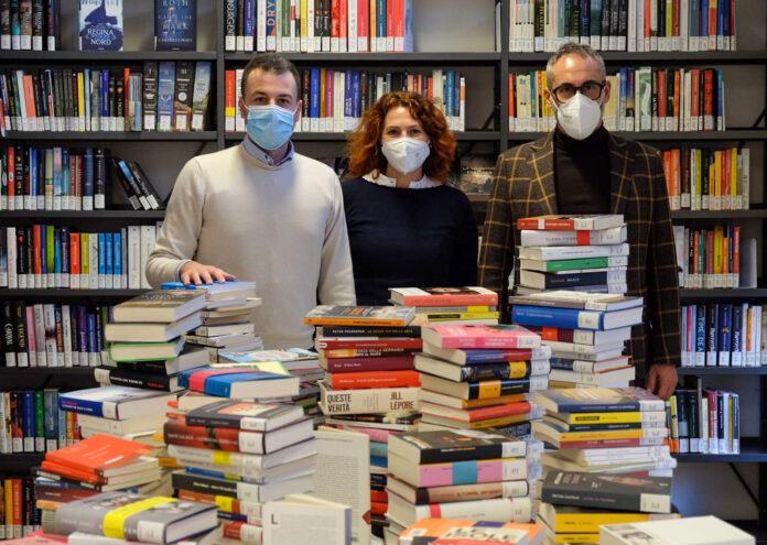 L'Assessore Venturini con alcuni libri consegnati in una biblioteca